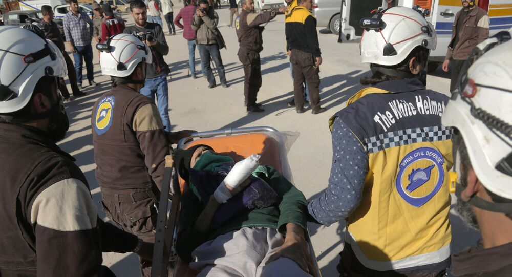 Syrian Civil Defence (known as the White Helmets) carry an injured man as Jaish al-Islam fighters and their families arrive from the former rebel bastion's main town of Douma at the Abu al-Zindeen checkpoint controlled by Turkish-backed rebel fighters near the northern Syrian town of al-Bab, on April 4, 2018