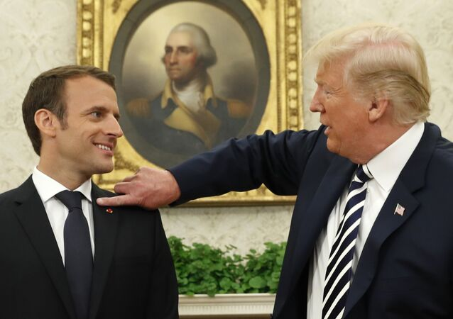 French President Emmanuel Macron (L) looks on as U.S. President Donald Trump flicks a bit of lint off his jacket during their meeting in the Oval Office following the official arrival ceremony for Macron at the White House in Washington, U.S., April 24, 2018.