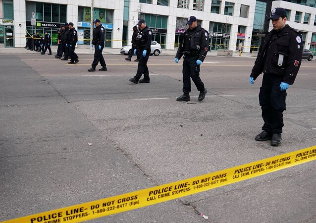 Police officers comb a street for evidence after a van struck multiple people along a major intersection in north Toronto, Ontario, Canada, April 24, 2018.