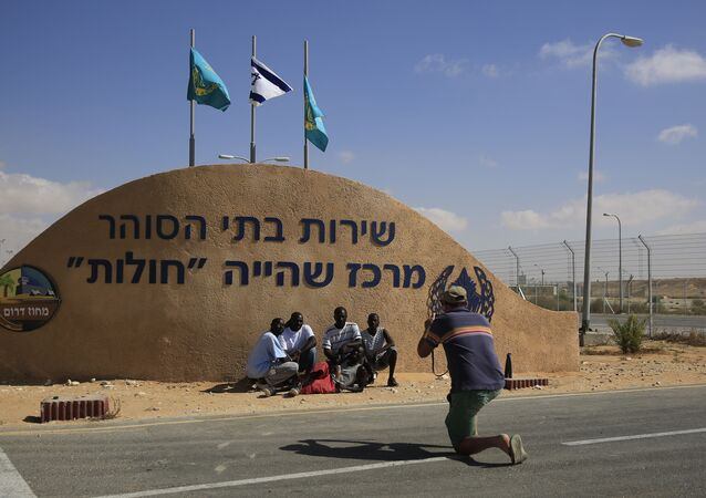 African migrants pose for a photograph in front of the Holot detention center in the Negev Desert, southern Israel. Tuesday, Sept. 23, 2014