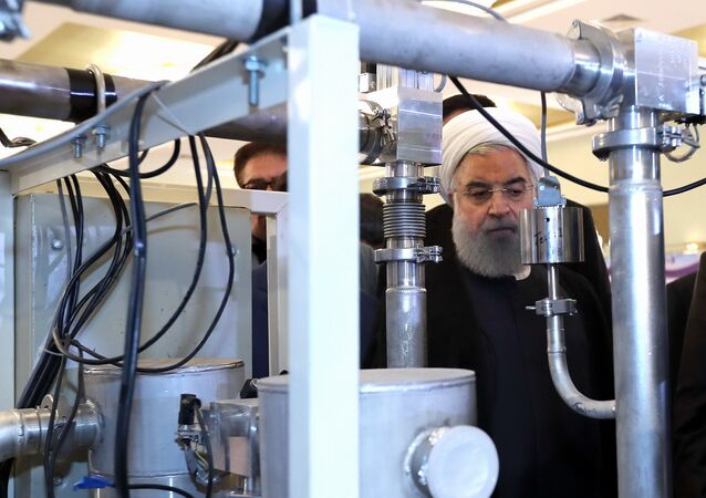 President Hassan Rouhani listens to explanations on new nuclear achievements at a ceremony to mark National Nuclear Day, in Tehran, Iran, Monday, April 9, 2018
