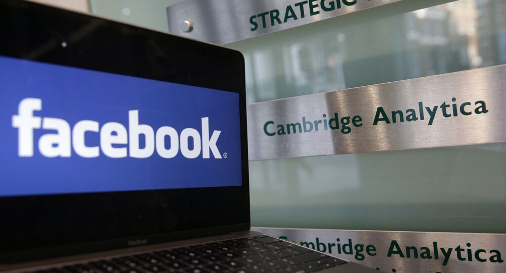 A laptop showing the Facebook logo is held alongside a Cambridge Analytica sign at the entrance to the building housing the offices of Cambridge Analytica, in central London on March 21, 2018