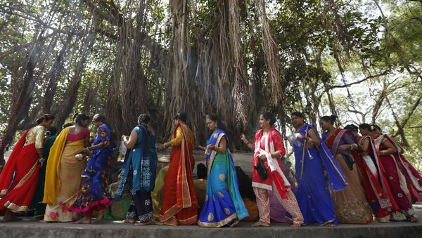 (File) Indian Hindu married women tie cotton threads around a Banyan tree as they perform rituals on the first day of Vat Savitri festival in Ahmadabad, India, Tuesday, June 6, 2017 - Sputnik International