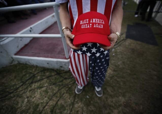 A man dressed in American flag clothes holds Make America Great Again hats.