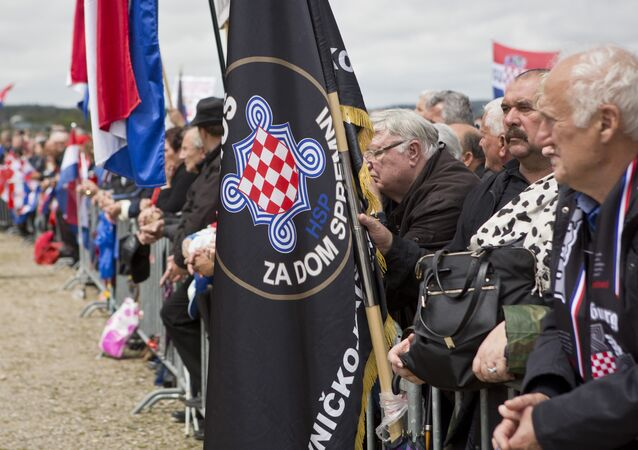 Visitors hold flags including a black one reading Za Dom Spremni or For Homeland Ready, a chant used by pro-nazis during WWII, attend a rally in Bleiburg, Austria, Saturday, May 14, 2016
