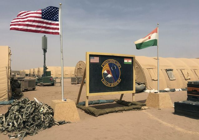 In this photo taken Monday, April 16, 2018, a U.S. and Niger flag are raised side by side at the base camp for air forces and other personnel supporting the construction of Niger Air Base 201 in Agadez, Niger.