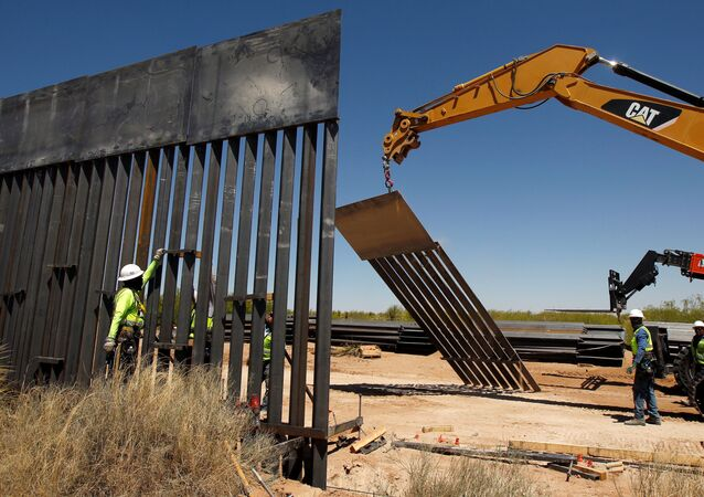 Construction workers are seen next to heavy machinery while working on new bollard wall in Santa Teresa, New Mexico, as seen from the Mexican side of the border in San Jeronimo, on the outskirts of Ciudad Juarez, Mexico April 23, 2018
