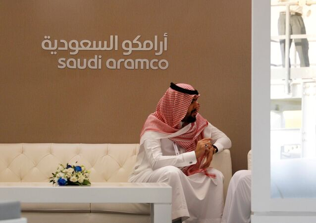 A Saudi Aramco employee sits in the area of its stand at the Middle East Petrotech 2016, an exhibition and conference for the refining and petrochemical industries, in Manama, Bahrain, September 27, 2016