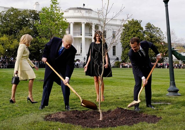 U.S. President Donald Trump and French President Emmanuel Macron shovel dirt onto a freshly planted oak tree as first lady Melania Trump and Brigitte Macron watch on the South Lawn of the White House in Washington, U.S., April 23, 2018