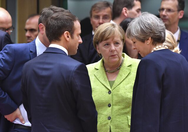 French President Emmanuel Macron, second left, speaks with German Chancellor Angela Merkel, center, and British Prime Minister Theresa May, right, during a round table meeting at an EU summit in Brussels on Thursday, June 22, 2017