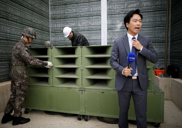 A reporter prepares a news report as South Korean soldiers dismantle loudspeakers that were set up for propaganda broadcasts near the demilitarized zone separating the two Koreas in Paju, South Korea, May 1, 2018.