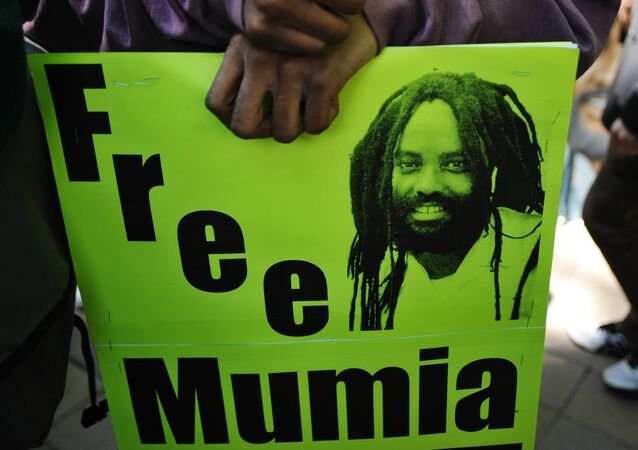 Protestors stand before an image of Mumia Abu-Jamal outside the US Department of Justice on April 24, 2012 in Washington, DC, calling for the release from prison of the ex-Black Panther militant, who was convicted for the killing of a white police officer in 1981 and sentenced to death.