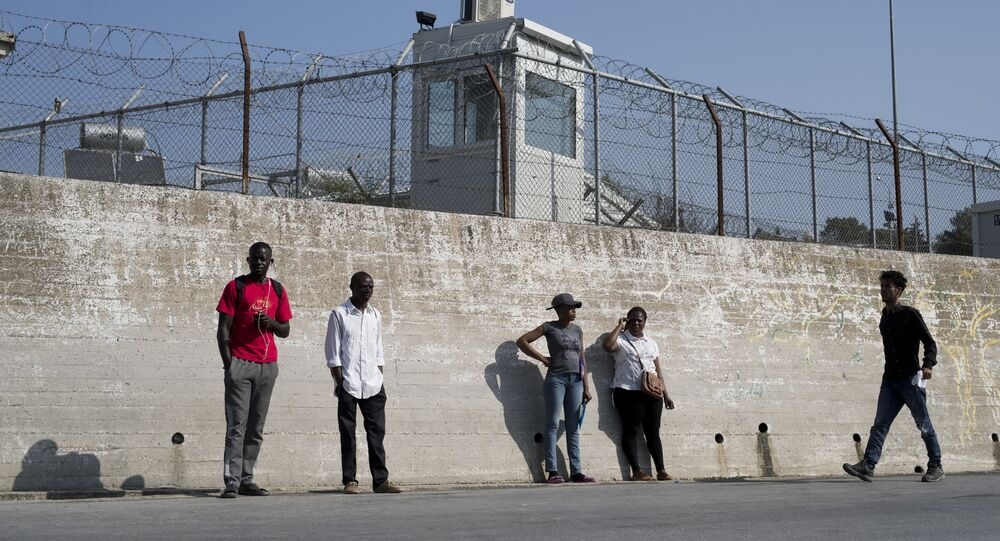 Migrants stand outside the walls of the Moria refugee camp on the northeastern Aegean island of Lesbos, Greece, Wednesday, May 2, 2018