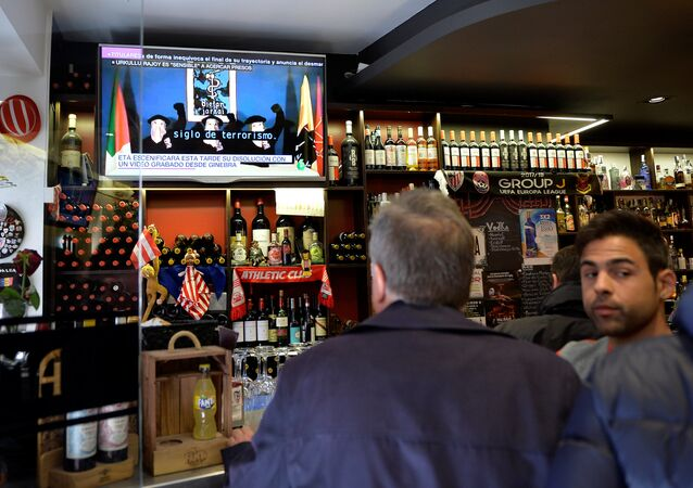 People drink in a bar while the television displays a video of Basque armed separatists ETA announcing their dissolution in Bilbao, Spain May 3, 2018
