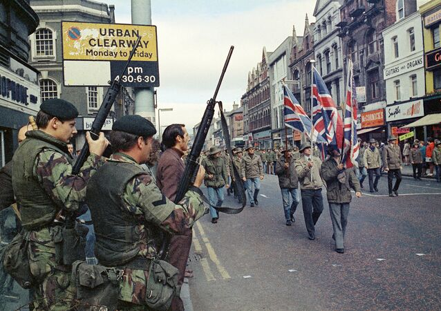 Under the watchful eyes of armed British troops, members of the Ulster Defence Association parade through Belfast, Northern Ireland in August 1972