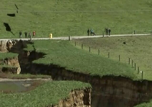 This image made from the May 2, 2018 video shows huge sinkhole on farm in Rotorua, New Zealand.