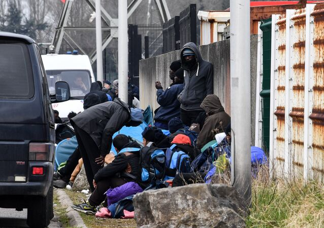 Migrants gather by the ringroad leading to the harbour on March 30, 2018 in Calais, near a police van patrolling (Rear L)