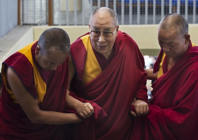 Tibetan spiritual leader the Dalai Lama is helped up the stairs by attendant monks as he arrives to participate in a dialogue between Russian scientists and Buddhist scholar at the Tsuglakhang temple in Dharmsala, India, Friday, May 4, 2018