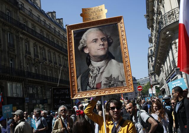 A protester carries a picture of French president Macron depicted as king Louis XIV during a protest in Paris, France, Saturday, May 5, 2018
