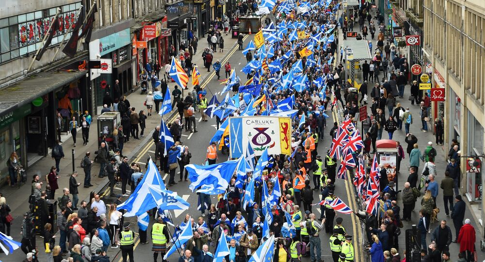 Anti-independence supporters wave Union Jack flags (R) as thousands of demonstrators carry Saltire flags, the national flag of Scotland, as they march in support of Scottish independence through the streets of Glasgow, on May 5, 2018