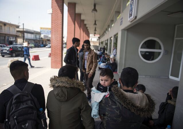 Migrants wait outside the police headquarters at the northern Greek city of Thessaloniki, on Friday, April 13, 2018