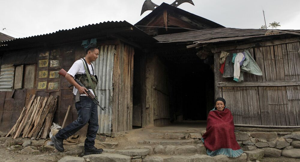 An armed cadre of the National Socialist Council of Nagaland (NSCN-IM), left, walks past an elderly woman sitting outside a traditional Naga hut, during a visit by the NSCN-IM General-Secretary Thuingaleng Muivah, at Viswema village, about 25 kilometers (16 miles) south of Kohima, capital of the northeastern Indian state of Nagaland (File)