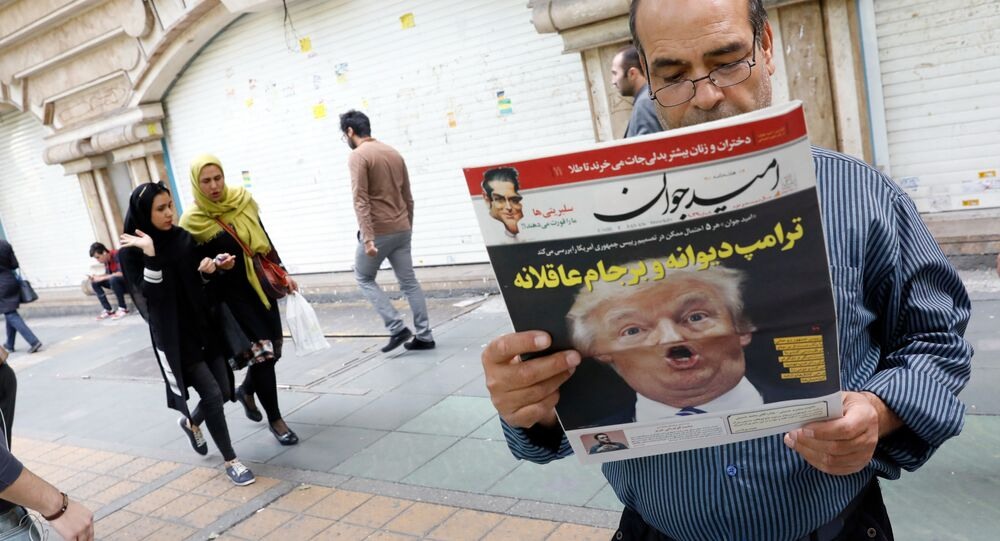 An Iranian man reads a copy of the daily newspaper 'Omid Javan' bearing a picture of US President Donald Trump with a headline that reads in Persian Crazy Trump and logical JCPOA (Joint Comprehensive Plan of Action), on October 14, 2017, in front of a kiosk in the capital Tehran