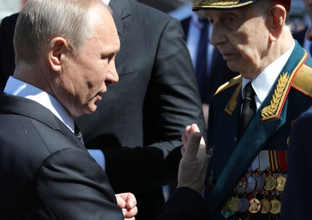 May 9, 2018. President of Russia and the Supreme Commander-in-Chief of the Russian Armed Forces Vladimir Putin with a veteran after the military parade to mark the 73rd anniversary of Victory in the Great Patriotic War of 1941-1945 on Moscow's Red Square. President of Serbia Aleksandar Vucic, background