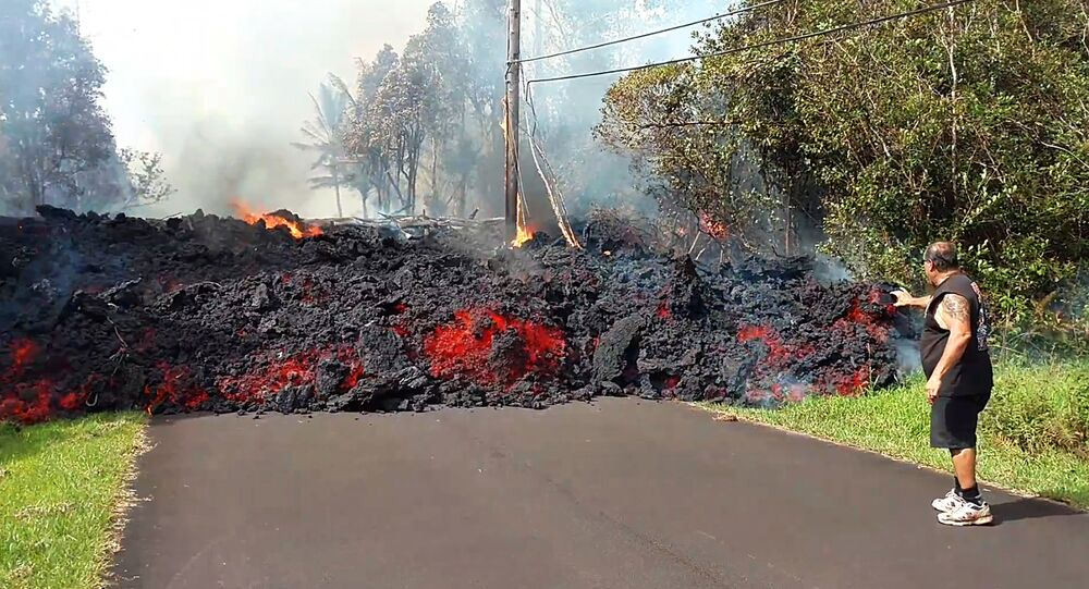 In this photo taken from video an unidentified man gets close to a lava flow advancing down a road in the Leilani Estates subdivision near Pahoa on the island of Hawaii Monday, May 7, 2018