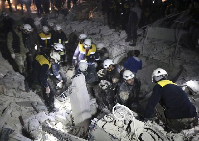 This photo provided on Sunday, Jan. 7, 2018 by the Syrian Civil Defense White Helmets, which has been authenticated based on its contents and other AP reporting, shows Civil Defense workers inspecting a damages building after a bombing that targeted the office of Ajnad al-Koukaz, a militant group consisting of foreign fighters mostly from the Caucuses and Russia, in Idlib, Syria