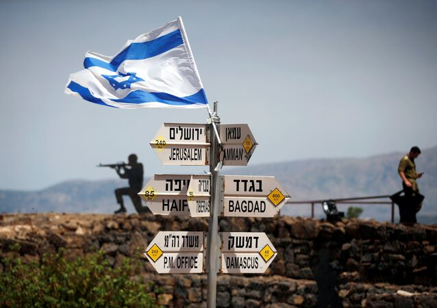 An Israeli soldier stands next to signs pointing out distances to different cities, on Mount Bental, an observation post in the Israeli-occupied Golan Heights that overlooks the Syrian side of the Quneitra crossing, Israel May 10, 2018