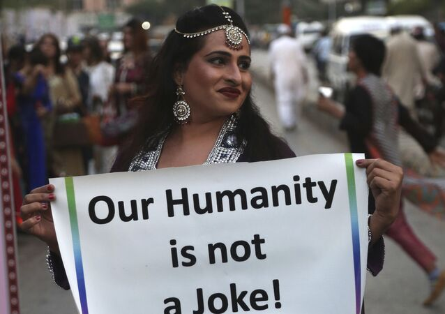 A member of the Pakistani transgender community holds up a sign, during a symbolic catwalk event, in Karachi, Pakistan, Monday, Nov. 20, 2017