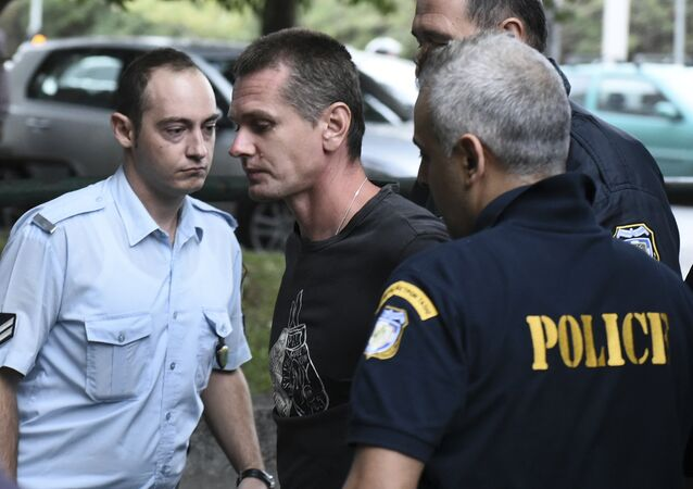A Russian man identified as Alexander Vinnik, center, is escorted by police officers to the courthouse at the northern Greek city of Thessaloniki on Friday, Sept. 29, 2017