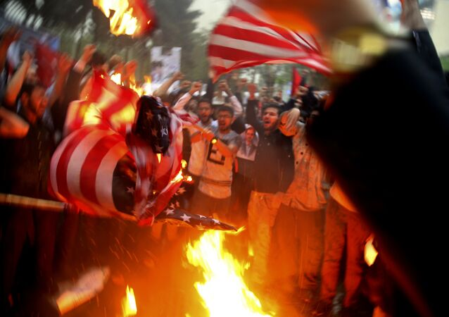 Iranian demonstrators burn representations of the U.S. flag during a protest in front of the former U.S. Embassy in response to President Donald Trump's decision Tuesday to pull out of the nuclear deal and renew sanctions, in Tehran, Iran, Wednesday, May 9, 2018
