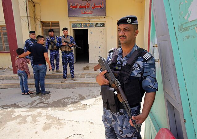 In this Wednesday, May 9, 2018 photo, Iraqi security forces guard a polling station in Baghdad, Iraq