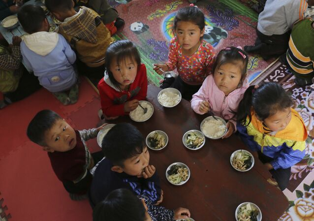 In this May 9, 2018 photo provided by the World Food Program (WFP), children eat a meal at a nursery and kindergarten where WFP provides food assistance in Sinwon county in North Korea's South Hwanghae province