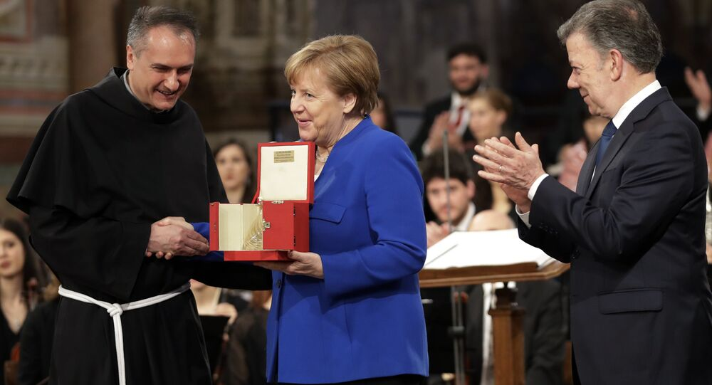 German Chancellor Angela Merkel, center, flanked by Colombian President Juan Manuel Santos, right, receives the St. Francis lamp peace prize by Father Mauro Gambetti during a ceremony inside Assisi's Basilica, Italy, Saturday, May 12, 2018