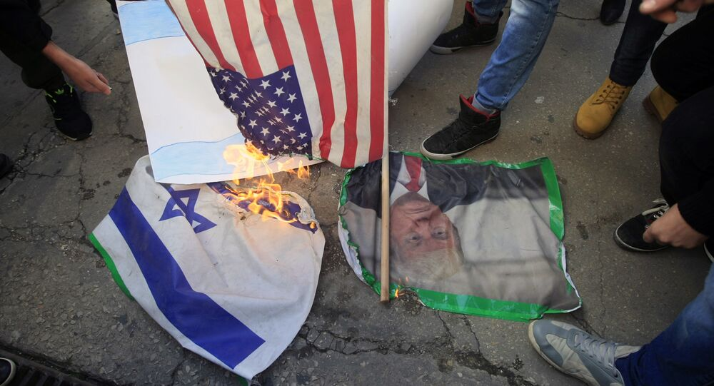 Lebanese and Palestinians students, burn a picture of U S. President Donald Trump, an American flag and an Israeli flag, as they take part in a protest at the Lebanese University, in the southern port city of Sidon, Lebanon, Thursday, Dec. 7, 2017, against U.S. President Donald Trump's decisions to recognize Jerusalem as the capital of Israel