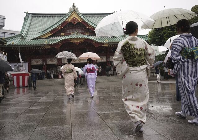 Kimono-clad visitors walk at the Kanda Myojin Shinto shrine in the rain during its festival in Tokyo Saturday, May 13, 2017