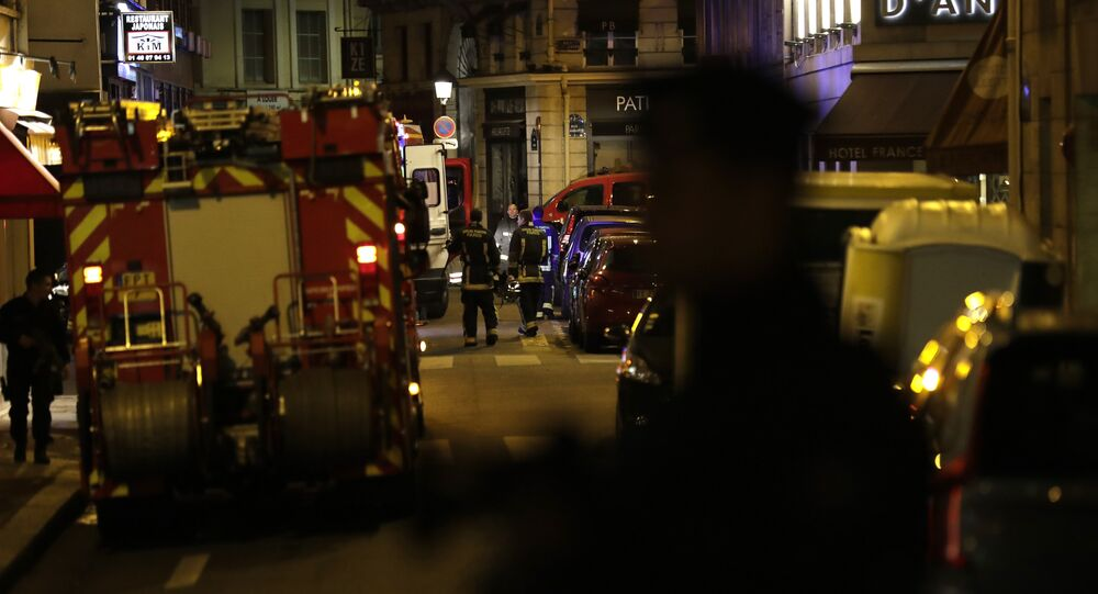 Policemen stand guard in Paris centre past firefighters vehicles after one person was killed and several injured by a man armed with a knife, who was shot dead by police in Paris on May 12, 2018