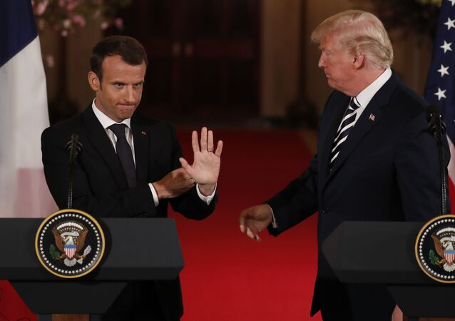 French President Emmanuel Macron waves to someone in the crowd as he and U.S. President Donald Trump conclude their joint news conference in the East Room of the White House in Washington, U.S., April 24, 2018