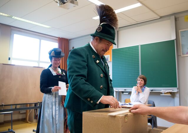 A man and a woman in traditional Bavarian dresses cast their ballots at a polling station in Unterwoessen near Rosenheim, southern Germany, during general elections on September 24, 2017