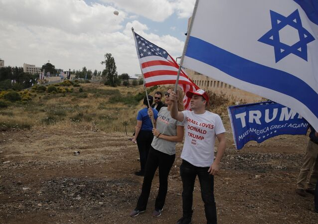 Israelis hold American and Israeli flags with the new U.S. embassy in the background in Jerusalem, Monday, May 14, 2018