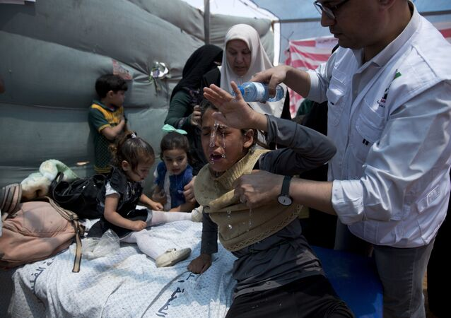 Medics treat Palestinian children suffering from teargas inhalation during a protest near Beit Lahiya, Gaza Strip, Monday, May 14, 2018