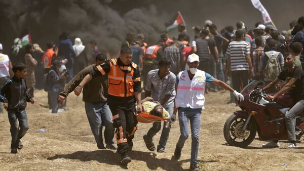 Palestinians carry a demonstrator injured during clashes with Israeli forces near the border between the Gaza strip and Israel east of Gaza City on May 14, 2018, as Palestinians readied for protests over the inauguration of the US embassy following its controversial move to Jerusalem - Sputnik International