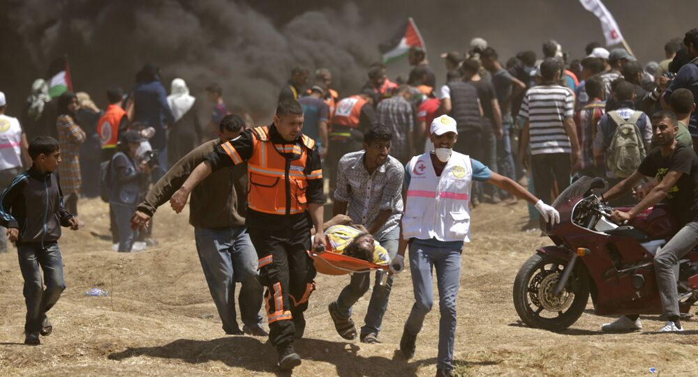 Palestinians carry a demonstrator injured during clashes with Israeli forces near the border between the Gaza strip and Israel east of Gaza City on May 14, 2018, as Palestinians readied for protests over the inauguration of the US embassy following its controversial move to Jerusalem