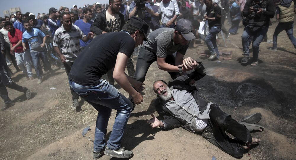 An elderly Palestinian man falls on the ground after being shot by Israeli troops during a deadly protest at the Gaza Strip's border with Israel, east of Khan Younis, Gaza Strip, 14 May, 2018