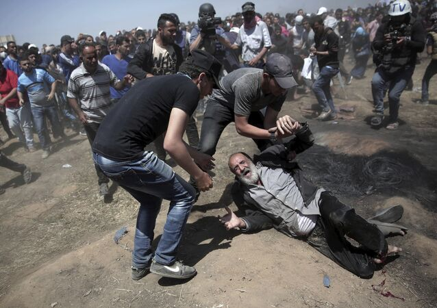 An elderly Palestinian man falls on the ground after being shot by Israeli troops during a deadly protest at the Gaza Strip's border with Israel, east of Khan Younis, Gaza Strip, Monday, May 14, 2018