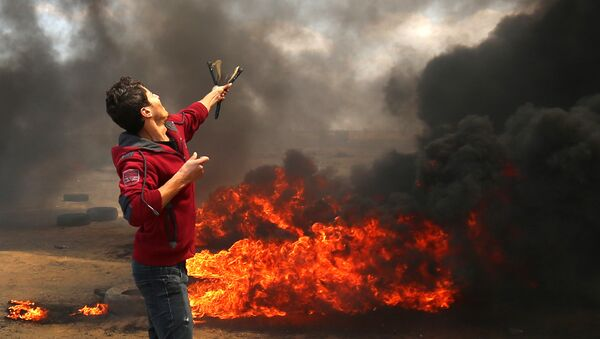 A Palestinian man uses a slingshot during clashes with Israeli forces along the border with the Gaza strip east of Khan Yunis on May 14, 2018, as Palestinians protest over the inauguration of the US embassy following its controversial move to Jerusalem - Sputnik International