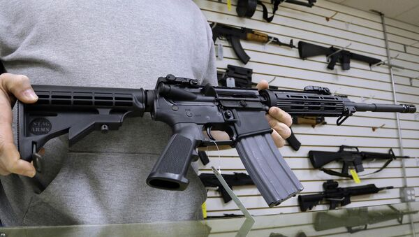 John Jackson, co-owner of Capitol City Arms Supply shows off an AR-15 assault rifle for sale Wednesday, Jan. 16, 2013 at his business in Springfield, Ill. - Sputnik International